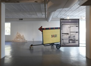 "From left to right: Assaf Evron, ""Untitled (Egyptian Embassy Tel Aviv),"" 2013. Dry wall, split-face blocks, and acrylic. 6′ x 5′; Conrad Bakker, ""Untitled Project: SIGN [Relax and Take Your Fucking Time],"" (2013), oil paint on carved wood, 82 x 108 x 58 inches; Aaron Van Dyke, ""Untitled"" (2013), inkjet print (double-sided), 42 x 64 inches. (all images courtesy of Hyde Park Art Center unless otherwise noted)"