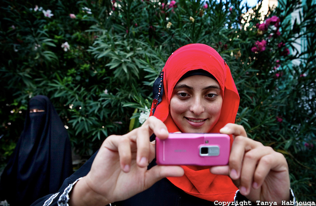 """Tanya Habjouqa, from the series """"Women of Gaza."""" """"An English literature student at the Islamic University in Gaza takes a break with fellow students. She is eager to apply her English skills and says that her dream is to travel the world. The siege on Gaza makes travel near impossible for the vast majority of Gazans."""" (all images courtesy of the artist unless otherwise noted)"""